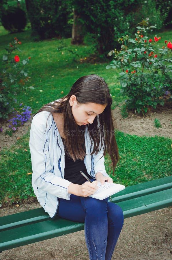 Een jong meisje zit op een bank in de tuin en trekt stock foto's
