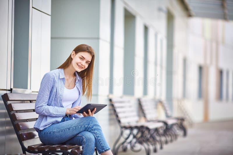 Een jong meisje zit op een bank met een tablet in haar handen en het glimlachen royalty-vrije stock fotografie