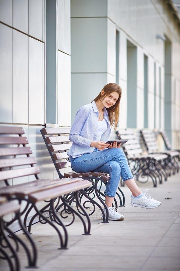 Een jong meisje zit op een bank met een tablet in hun handen en het glimlachen stock fotografie