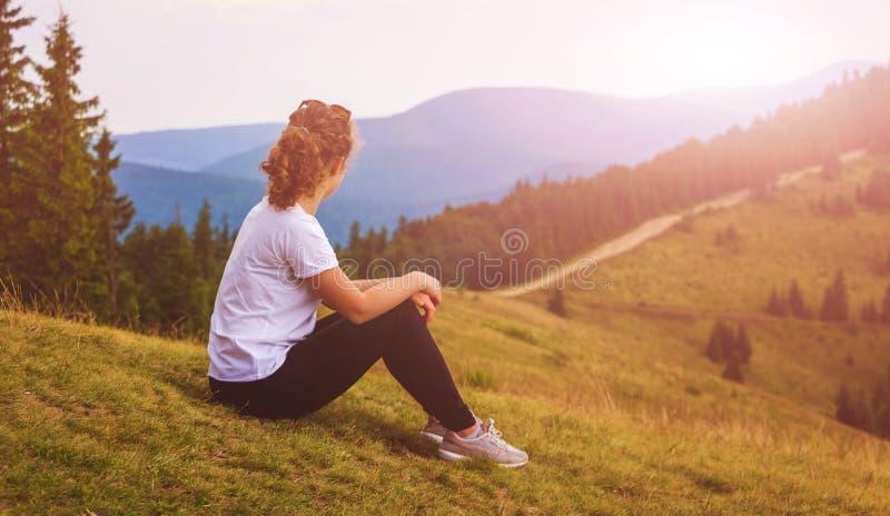 Een jong meisje zit op de helling van de berg en bekijkt sunrise_ royalty-vrije stock fotografie