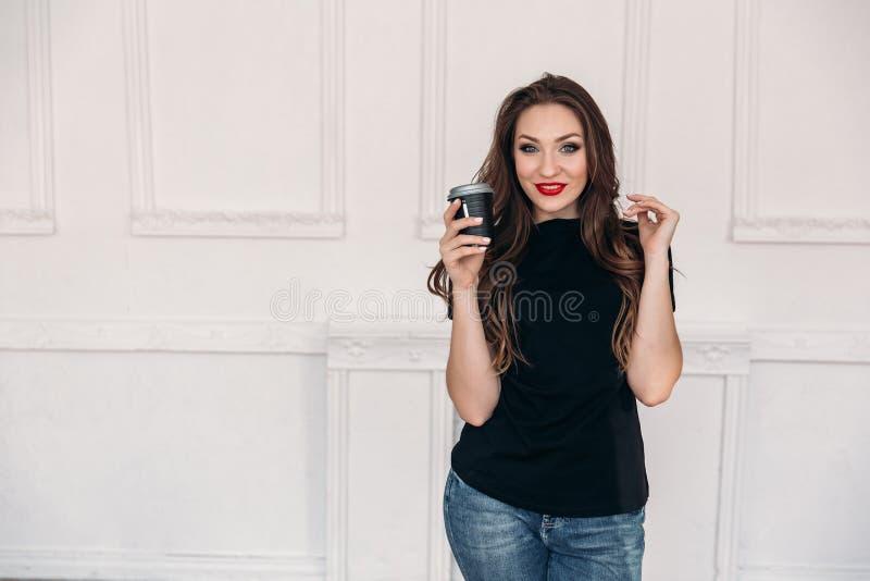 Een jong mooi glimlachend meisje in een zwarte T-shirt draagt donkere jeans en schildert haar lippen met rode lippenstift, begint royalty-vrije stock foto