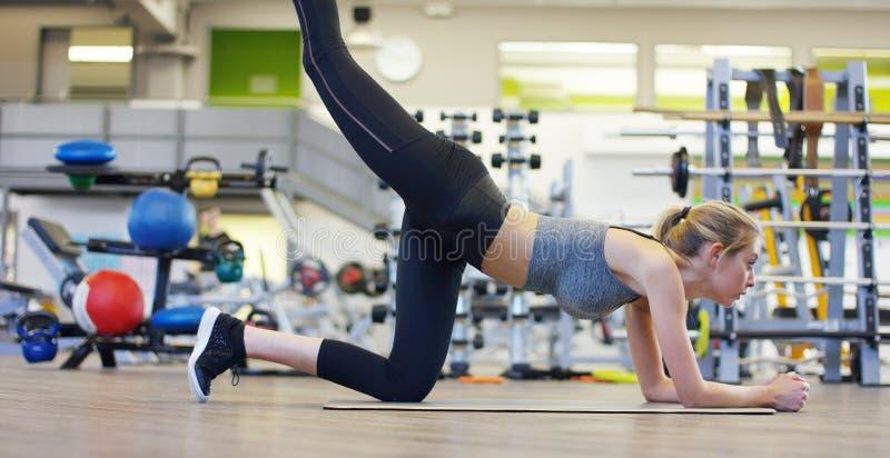 Een jong mooi meisje in een gymnastiek, die op haar handen leunen, schudt de pers, die lange stappen maken, die haar knieën buige stock afbeelding