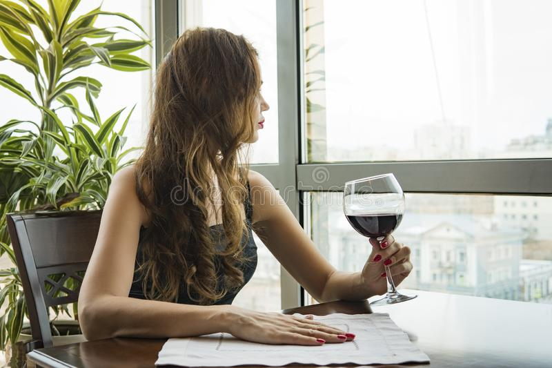 Een jong mooi meisje in een zwarte kleding zit in een restaurant en drinkt wijn van een glas sluit omhoog van jonge vrouw wat royalty-vrije stock afbeeldingen
