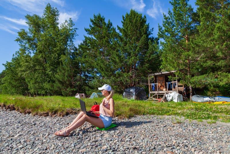 Een jong mooi vrouwenblonde in de borrels van een wit GLB en van het denim zit op de rotsachtige kust van de rivier met laptop op stock foto's