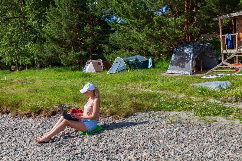 Een jong mooi vrouwenblonde in de borrels van een wit GLB en van het denim zit op de rotsachtige kust van de rivier met laptop op royalty-vrije stock foto's