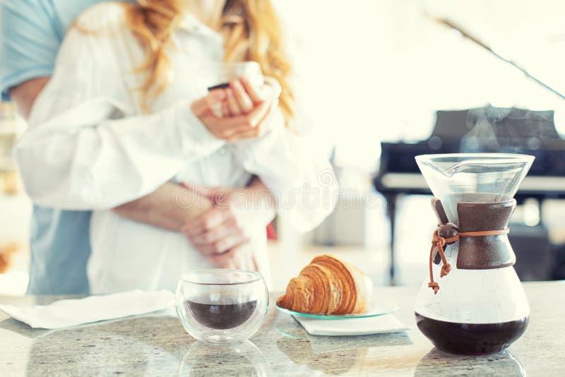 Een jong paar geknuffel in de keuken, giet over koffiezetapparaat op het voorplan, commerciële koffie stock foto's