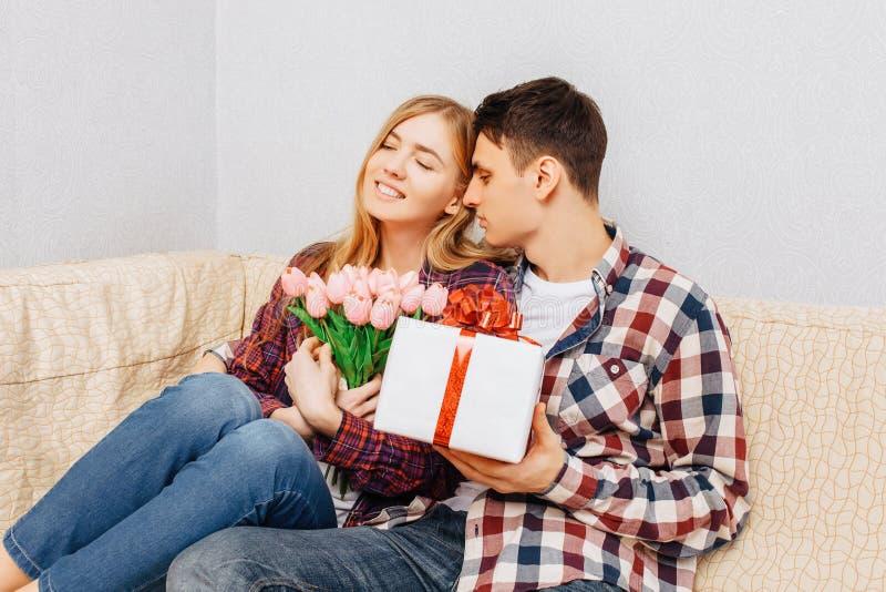 Een jong paar in liefde, een man wenst een vrouw door haar een boeket van tulpen en een gift geluk te geven, thuis zittend met de stock foto's