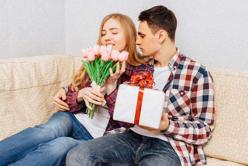 Een jong paar in liefde, een man wenst een vrouw door haar een boeket van tulpen en een gift geluk te geven, thuis zittend met de royalty-vrije stock foto