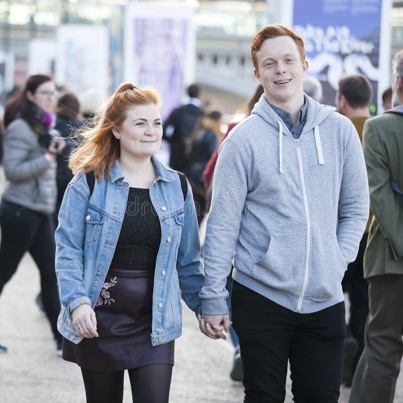 Een jong paar loopt onderaan de handen van de straatholding royalty-vrije stock fotografie