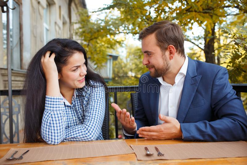Een jong paar spreekt in een koffie outdoors stock foto's