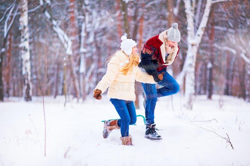 Een jong paar stelt pret in de sneeuw in een de winterpark in werking stock afbeelding
