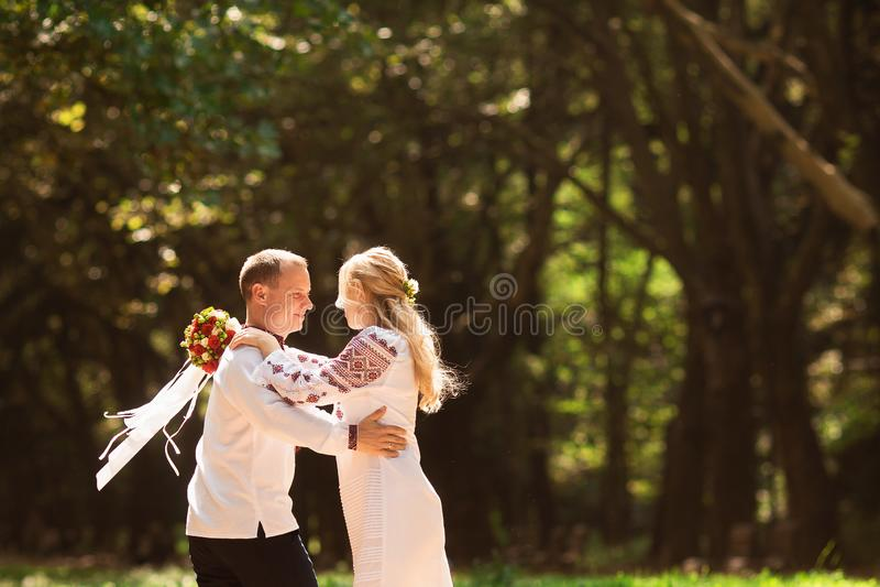 Een jong paar in een traditioneel Oekraïens kledings whith boeket geniet van de zonnige dag bij Stryisky-Park in Lviv royalty-vrije stock foto