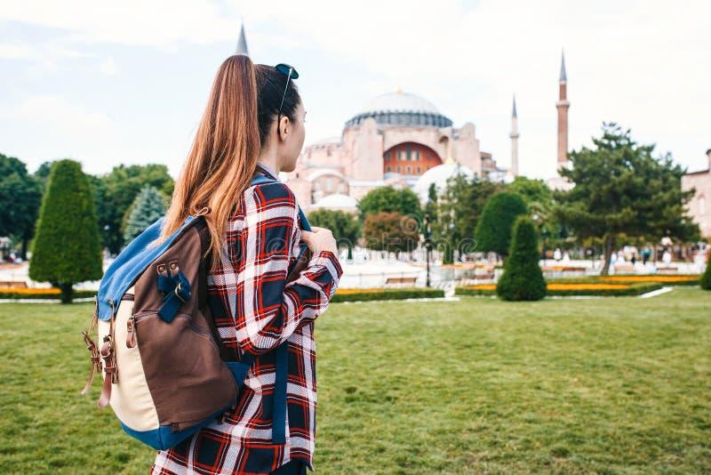 Een jong reizigersmeisje met een rugzak in Sultanahmet-Vierkant naast de beroemde Aya Sofia-moskee in Istanboel in Turkije royalty-vrije stock foto's