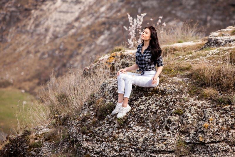 Een jong reizigersmeisje zit op de bovenkant van vallei Het jonge wilde leven van de meisjesliefde, reis, vrijheid stock foto's
