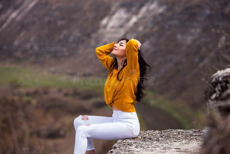 Een jong reizigersmeisje zit op de bovenkant van vallei Het jonge wilde leven van de meisjesliefde, reis, vrijheid royalty-vrije stock fotografie