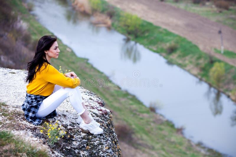 Een jong reizigersmeisje zit op de bovenkant van vallei Het jonge wilde leven van de meisjesliefde, reis, vrijheid royalty-vrije stock foto's