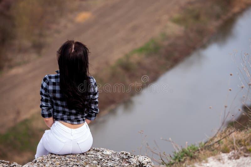 Een jong reizigersmeisje zit op de bovenkant van vallei Het jonge wilde leven van de meisjesliefde, reis, vrijheid royalty-vrije stock afbeelding