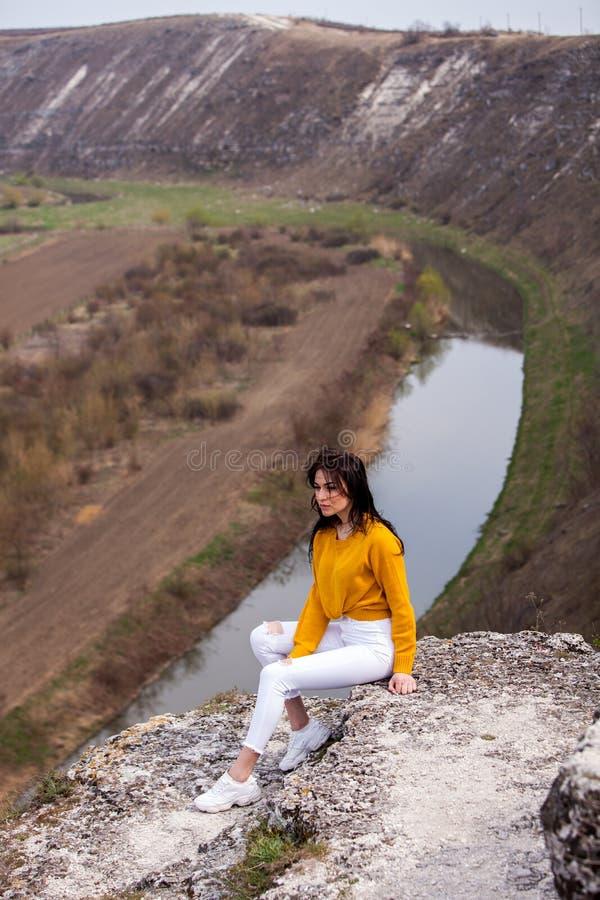Een jong reizigersmeisje zit op de bovenkant van vallei Het jonge wilde leven van de meisjesliefde, reis, vrijheid stock fotografie
