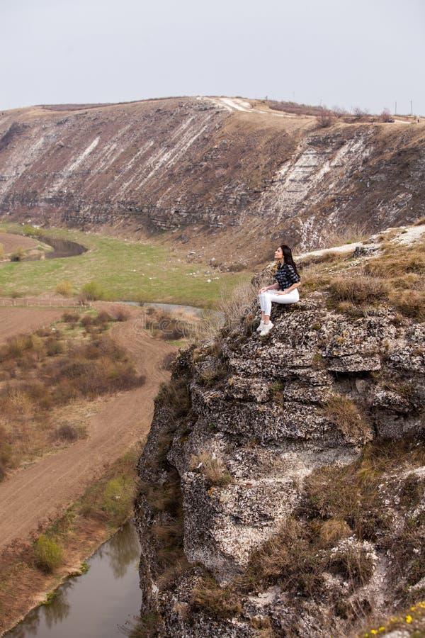Een jong reizigersmeisje zit op de bovenkant van vallei Het jonge wilde leven van de meisjesliefde, reis, vrijheid stock afbeeldingen