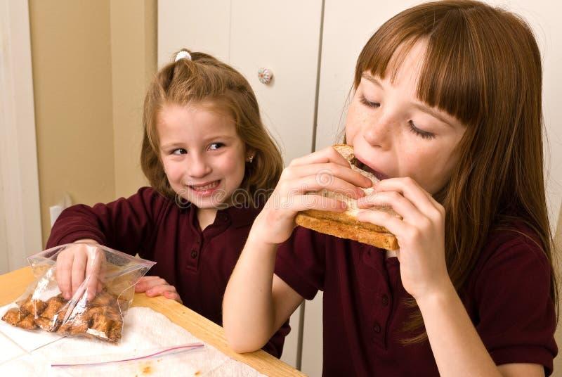 Jonge schoolmeisjes die lunch eten royalty-vrije stock afbeeldingen