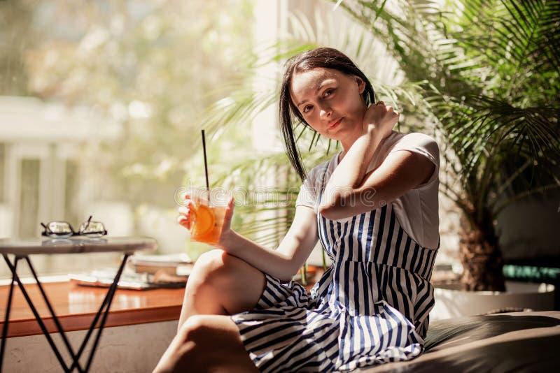 Een jong slank glimlachend meisje met donker haar, gekleed in toevallige uitrusting, zit bij de lijst en drinkt koffie in een com stock afbeeldingen