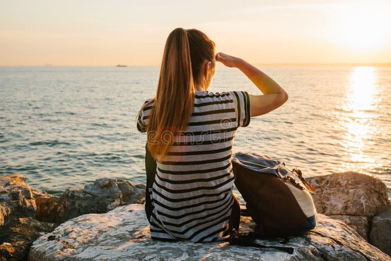 Een jong toeristenmeisje met een rugzak zit op de rotsen naast het overzees bij zonsondergang en onderzoekt de afstand rust stock foto's