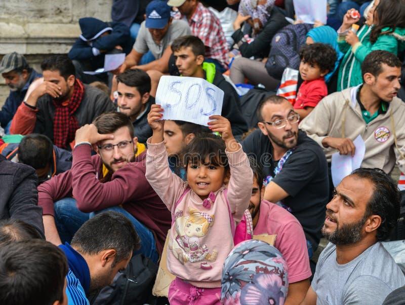 Een jong vluchtelingsmeisje steunt een S.O.S.teken bij Keleti-Spoorpost, Boedapest in September 2015 stock foto's