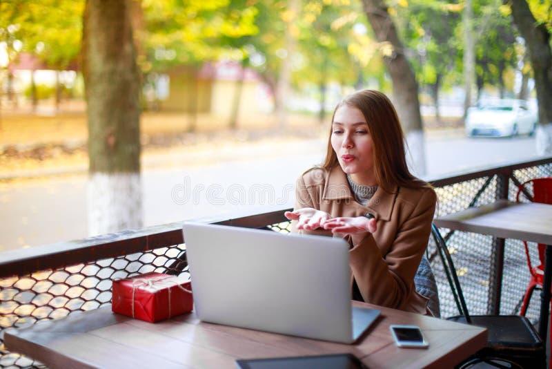 Een jong, vrolijk meisje in een openluchtkoffie zit bij een lijst met een laptop en giftvakje royalty-vrije stock foto's
