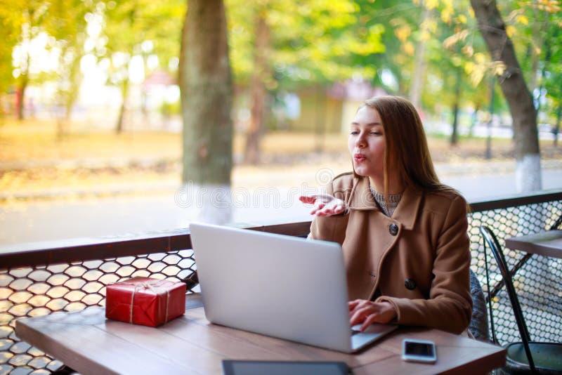 Een jong, vrolijk meisje in een openluchtkoffie zit bij een lijst met een laptop en giftvakje stock fotografie