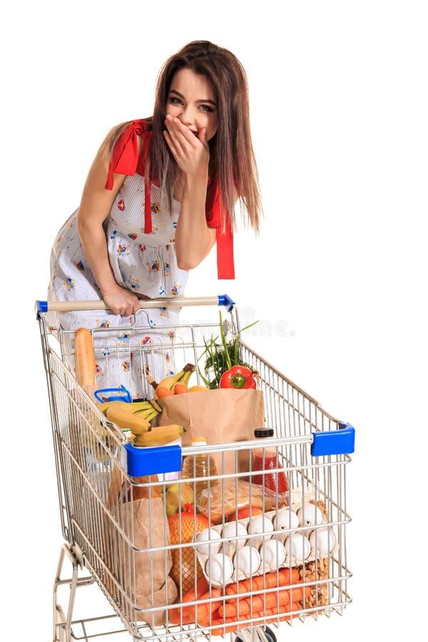 Een jong wijfje die een boodschappenwagentjehoogtepunt met kruidenierswinkels duwen die op witte achtergrond wordt geïsoleerd Een stock foto