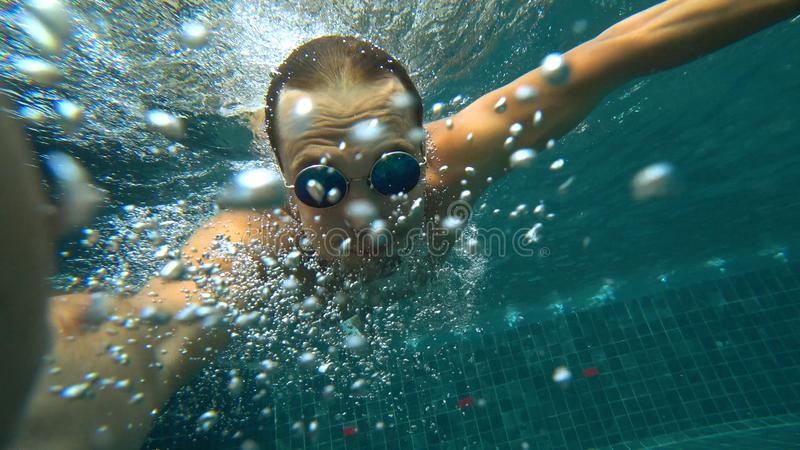 Een jong wit knap mannetje die een onderwaterselfie op een actiecamera doen Portret van een jonge mens met glazen het nemen royalty-vrije stock foto