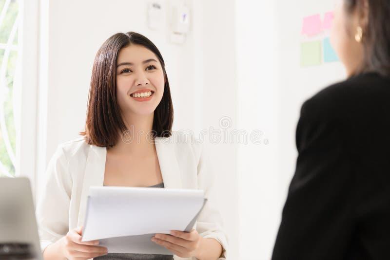 Een jonge, aantrekkelijke aziatische vrouw interviewt voor een baan Haar interviewers zijn divers royalty-vrije stock foto