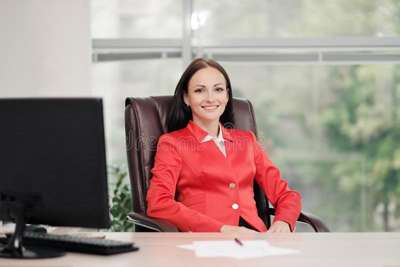 Een jonge aantrekkelijke Kaukasische blonde vrouw in een rood pak zit bij een bureau in een helder bureau Portret van a stock afbeeldingen