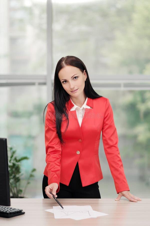 Een jonge aantrekkelijke Kaukasische blonde vrouw in een rood pak zit bij een bureau in een helder bureau Portret van a royalty-vrije stock foto's