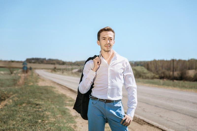 Een jonge aantrekkelijke mens bevindt zich bij middag op een zonovergoten landelijke weg stock foto