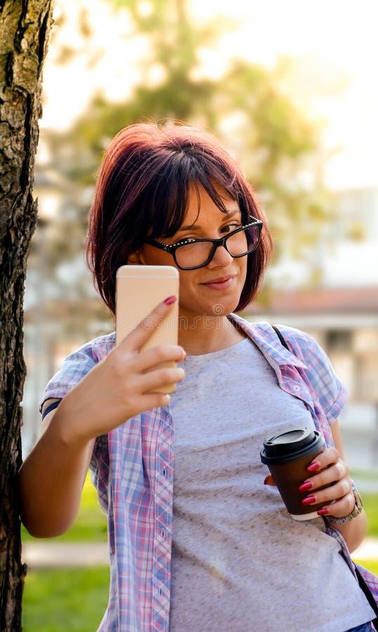 Een jonge aantrekkelijke vrouw die een zelfportret maken en een kop van koffie houden royalty-vrije stock foto