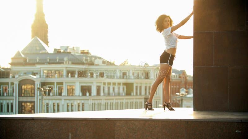 Een jonge aantrekkelijke vrouw met krullend haar die zich op de verhoging in de stad bevinden - heldere zonsondergang royalty-vrije stock foto