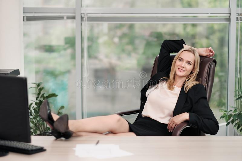 Een jonge aantrekkelijke vrouw in pak zit bij een bureau Rekt zich en ontspant op stoel uit De voeten zijn op lijst Rust van stock afbeelding