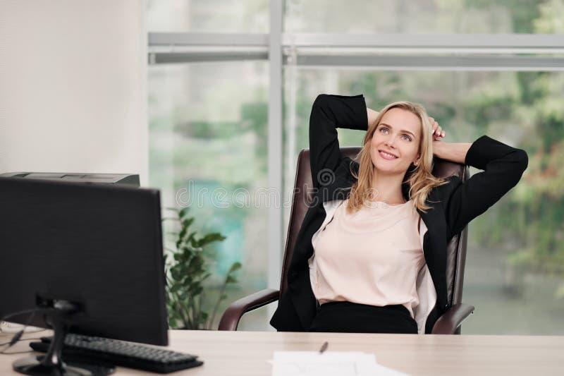 Een jonge aantrekkelijke vrouw in pak zit bij een bureau Rekt zich en ontspant op stoel uit De voeten zijn op lijst Rust van royalty-vrije stock foto