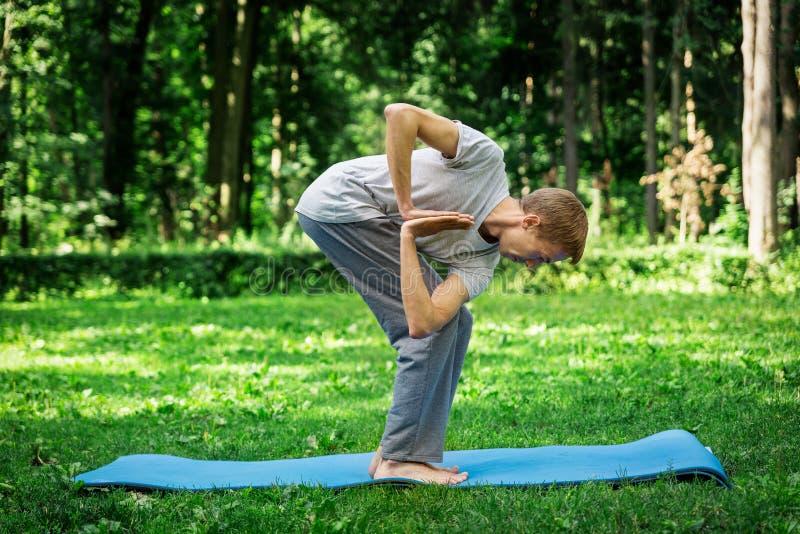 Een jonge aantrekkelijke yoga van mensenpraktijken in aard en mediteert in de lotusbloempositie inzake een groen gazon Weergeven  royalty-vrije stock afbeeldingen