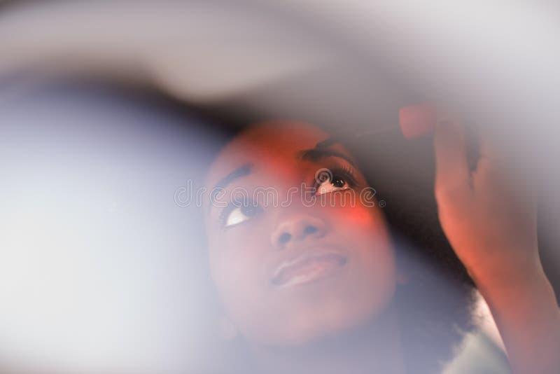 Een jonge Afrikaans-Amerikaanse vrouwenmake-up in de auto royalty-vrije stock afbeeldingen