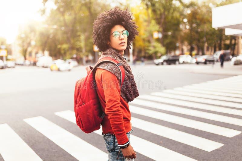 Een jonge Afrikaanse Amerikaanse mens met een rode rugzak kruist een zebrapad in een stad stock foto