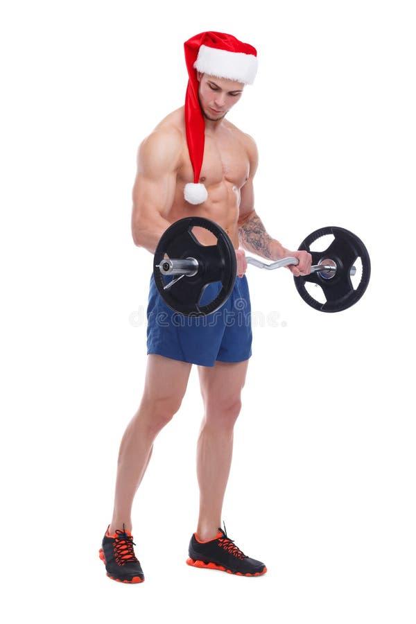Een jonge atletische hoed van kerelsanta, pompen de bicepsen met een barbell Geïsoleerde royalty-vrije stock afbeeldingen