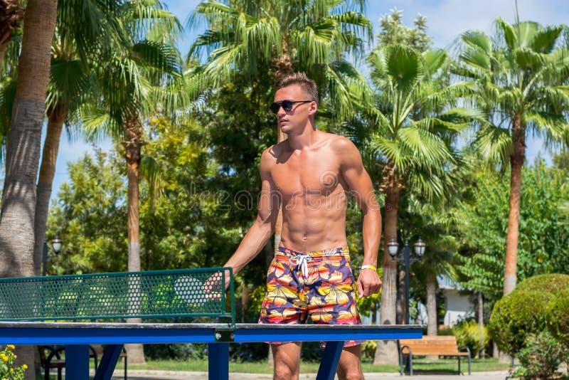Een jonge atletische mens speelt pingpong zonder overhemden in een park stock fotografie