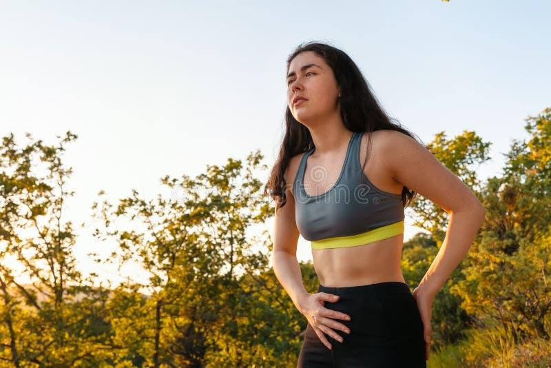 Een jonge atletische vrouw ervaart lager achter of buikpijn terwijl het uitoefenen Het concept sporten en sportblessures royalty-vrije stock afbeeldingen