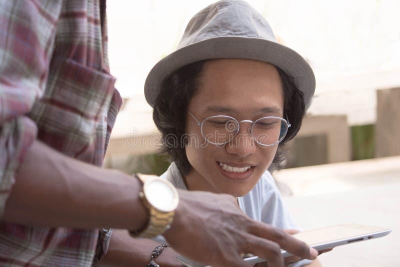 Een jonge Aziatische mens met hoed en glazen die terwijl iets met vriend bespreek die een tablet tonen glimlachen royalty-vrije stock afbeelding