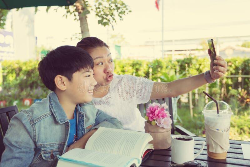 Een jonge Aziatische moeder maakt selfie met haar weinig leuke zoon stock foto