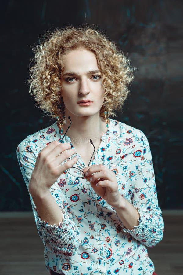Een jonge blonde man androgyn in het beeld van een aantrekkelijke vrouw kleedde zich in een bloemenoverhemd, royalty-vrije stock foto