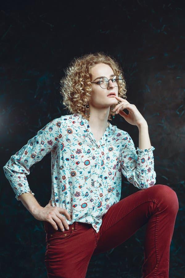 Een jonge blonde man androgyn in het beeld van een aantrekkelijke vrouw kleedde zich in een bloemenoverhemd, het stellen, de lipp royalty-vrije stock foto's