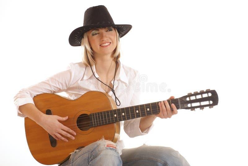 Een jonge blonde veedrijfster die op een coustic gitaar speelt stock foto's